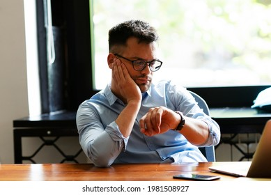 Tired businessman working at his laptop. Businessman looks at a wristwatch in the office.