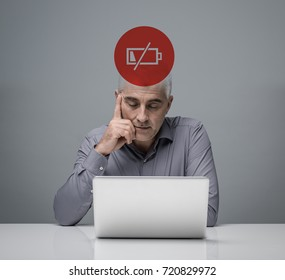 Tired businessman working with a laptop with low charge icon, stress and overwork concept