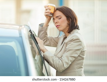 Tired businesswoman with a cup of coffee outdoors
