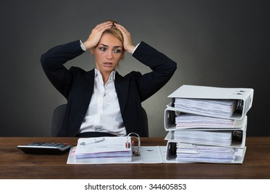 Tired businesswoman with hands on head sitting at desk over gray background