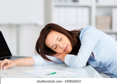 Tired businesswoman having a nap at her desk with her head lying on her arm facing the camera