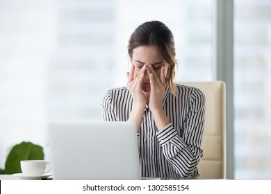 Tired businesswoman massaging eyes feeling strain fatigue headache relieving pain, exhausted female worker suffering from migraine eyestrain after computer work, eyesight problem, overwork concept