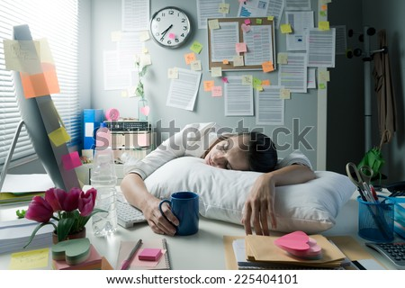Tired businesswoman at office desk waking up with pillow and coffee.
