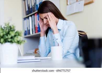 Tired businesswoman in office working on laptop computer - under pressure