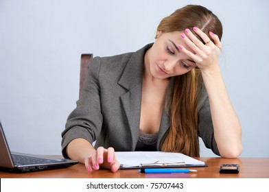 Tired businesswoman reading document at the office