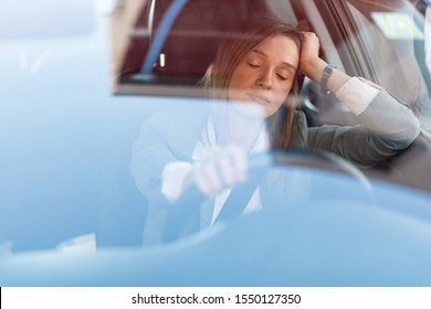 Tired businesswoman resting with eyes closed wile driving a car and being stuck in traffic jam.