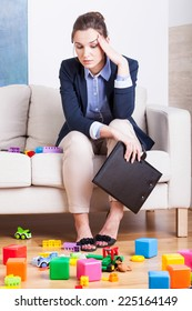 Tired businesswoman in room full of kids toys