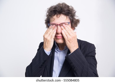 Tired businesswoman rubbing eyes behind glasses