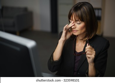 Tired Businesswoman Sitting at her Table, Takes Off her Eyeglasses and Rubs her Eyes