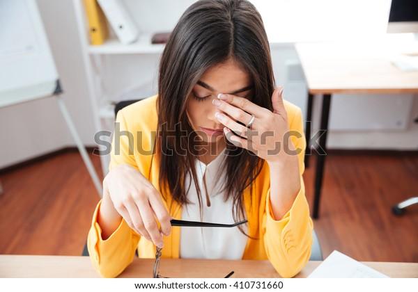 Femme d'affaires fatiguée assise au bureau