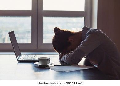 Tired businesswoman sleeping on table in office. Young exhausted girl working from home. Woman using laptop. Entrepreneur, business, freelance work, student, stress, work from home concept