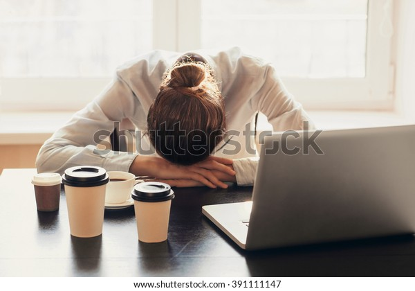 Tired businesswoman sleeping on table in office. Young overworked exhausted girl working from home. Woman using laptop. Entrepreneur, business, freelance work, student, stress, work from home concept