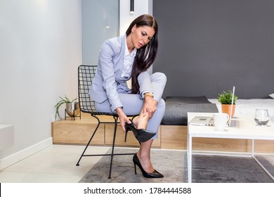 Tired businesswoman woman sitting on chair and taking shoes off after hard day at work. Businesswoman taking off high heels shoes after work at home.
