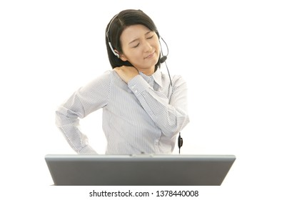Tired call center operator who has a shoulder pain.