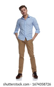 Tired casual man holding eyes closed and hands in pockets while wearing shirt and standing on white studio background