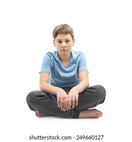 Tired caucasian 12 years old childen boy in a blue t-shirt sitting in a lotus position, full shot composition isolated over the white background