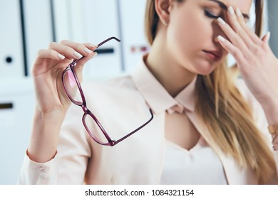 Tired Caucasian businesswoman holding eyeglasses and massaging nose bridge. Girl feeling discomfort from long wearing glasses at workplace.