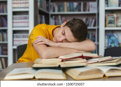 Tired caucasian guy having nap on books stack, being exhausted during preparing for exams