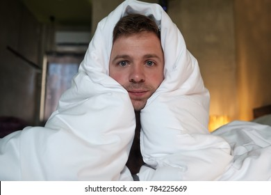 The tired caucasian man lay on the bed and looks ahead with pretty eyes. He wrapped his head in a blanket. Fatigue of health problems or stress at work