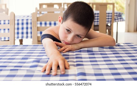 Tired child resting on table in cafe dining restaurant.