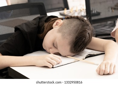Tired child sleeping while studying in the primary school classroom