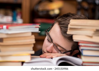 Tired child sleeping while studying. Boy with glasses studying asleep.
