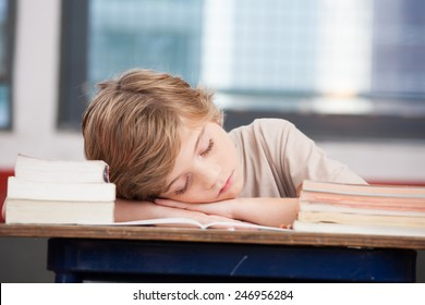 Tired child sleeping while studying in the primary school classroom.