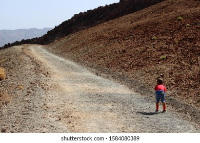 A tired child walking through the dry arid hot landscapes along the hiking trail on a climbing trekking up to the Mount Teide via Montana Blanca, Teide National Park, Tenerife, Canary Islands, Spain.