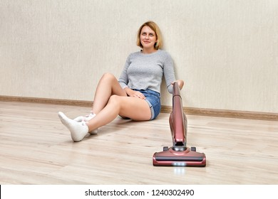 Tired cleaning lady is vacuuming sitting on the floor with help of cordless stick vacuum with led lights on.