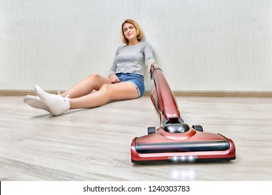 Tired cleaning woman is sitting on the floor and cleaning dust with modern red upright vacuum cleaner with led lights on.