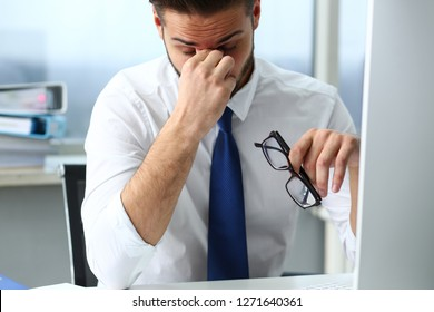 Tired clerk at laptop pc workplace wearing glasses hold face in arms not feeling well portrait in office. White collar worker sad freelance employment fail study coach training out low energy down