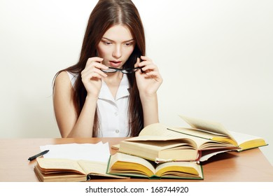 Tired College student girl in glasses with books at the desk