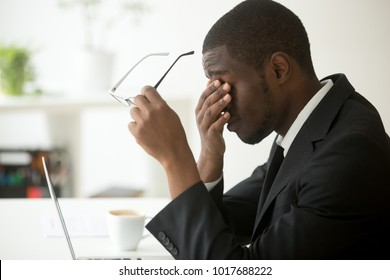 Tired of computer african businessman taking off glasses feels eye strain fatigue after long office work on laptop, exhausted overworked stressed depressed black man having bad sight vision problem