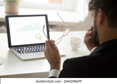 Tired of computer work businessman taking off glasses feeling eyestrain in front of laptop, employee having bad eyesight vision problem, eyes fatigue and overwork concept, rear over the shoulder view
