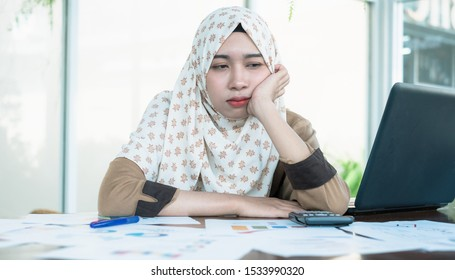 Tired confused bored and headache Thai young muslim woman worker or businessman wearing hijab while reading graph and chart report documents.