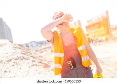 Tired construction worker wiping forehead at site