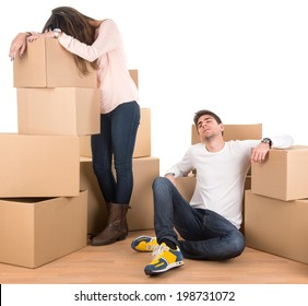 Tired couple with boxes moving into new home apartment