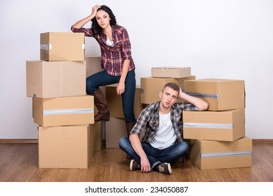 Tired couple with boxes are moving into new apartment.