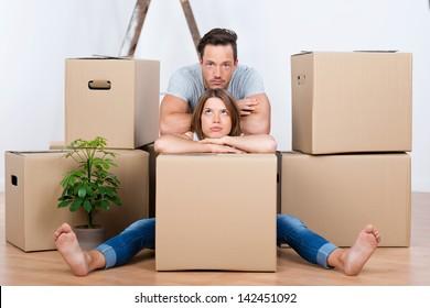 Tired couple sitting between many boxes in their new home