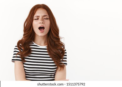 Tired cute redhead girl feeling tired, yawning from fatigue, close eyes looking sleepy, wake up early morning, wanna coffee, standing white background exhausted and bored, white background