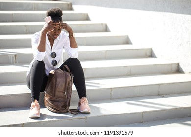 Tired dark-skinned touris female with Afro haircut wearing white t-shirt resting at stairs after a long walk trip in hot summer city, looking down feeling exhausted and drained.