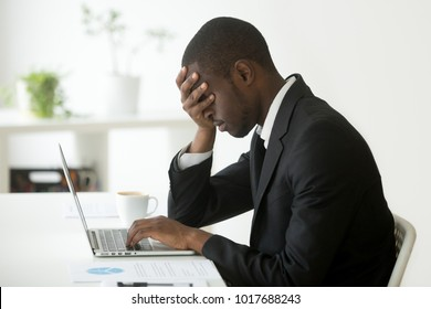 Tired depressed black businessman at workplace frustrated by business failure feeling exhausted covering face with hand, upset sleepy african office worker having nap dozing at work with laptop