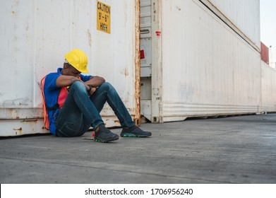 Tired  depressed black foreman worker working at Container cargo harbor to loading containers. African dock male staff fall asleep for Logistics import export shipping concept.