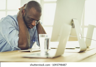 Tired or depressed businessman sitting at the desk with laptop
