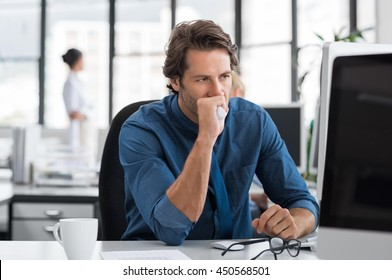 Tired and depressed businessman sitting in office at the table. Tensed businessman with hand on mouth staring at computer screen. Stressed business man thinking about solution at computer.