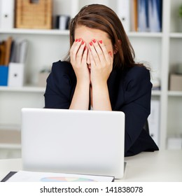 Tired or depressed businesswoman sitting at her desk behind her laptop with her hands covering her eyes