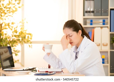 Tired and depressed doctor in medical office drinking coffee touch bridge of nose. mixed race asian chinese model. medical and healthcare concept.