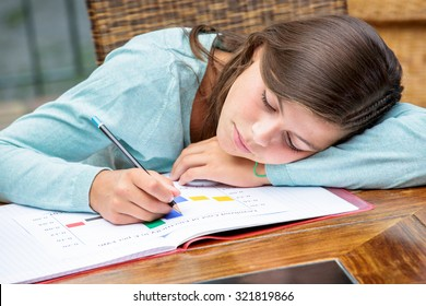 Tired or despondent young girl do homework lying on a table