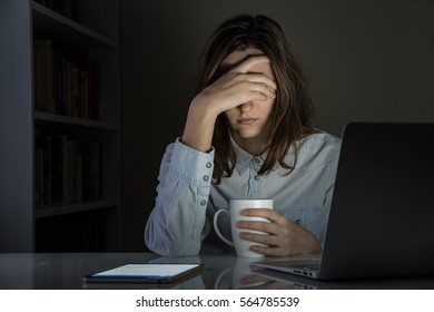 Tired and disappointed female person at home office workplace late at night. Sleepy woman holds cup of coffee or tea sitting at laptop computer and tablet PC in room late in the evening