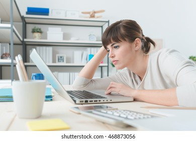 Tired disappointed woman working at office desk with a laptop, connection and computer problems concept